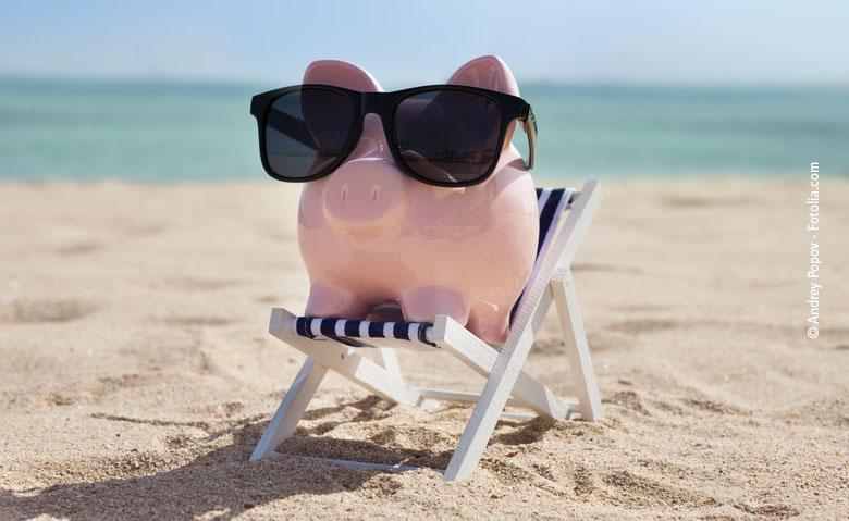 Ein Sparschwein liegt mit Sonnenbrille in einem Liegestuhl am Strand